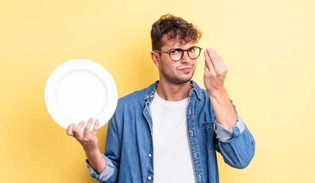 お金を払うように言って、capiceまたはお金のジェスチャーをしている若いハンサムな男。空の皿の概念