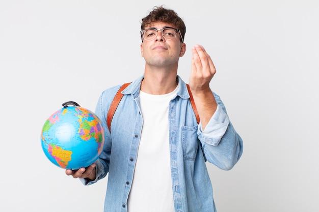 젊고 잘생긴 남자가 돈을 지불하라고 말하고 돈을 벌거나 몸짓을 합니다. 세계 지도를 들고 있는 학생