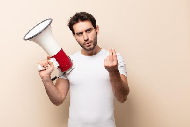 Молодой красивый мужчина делает капризный или денежный жест, говоря вам, чтобы вы заплатили свои долги!