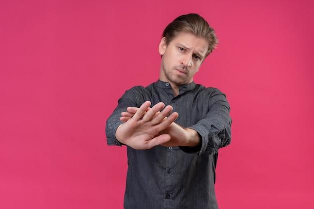 ピンクの壁の上に立って眉をひそめている手で停止ジェスチャーを作る若いハンサムな男