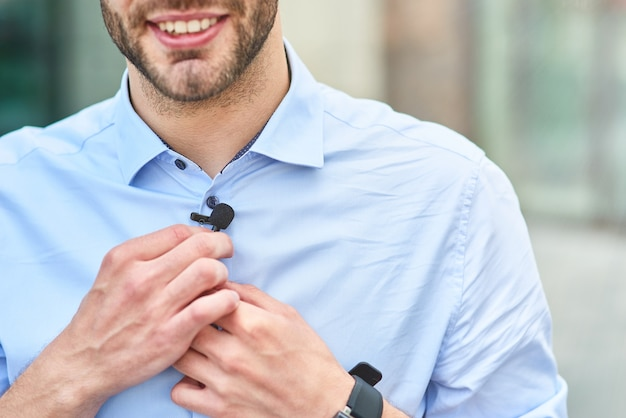Young handsome man male blogger adjusting small lavalier microphone on his shirt and smiling while