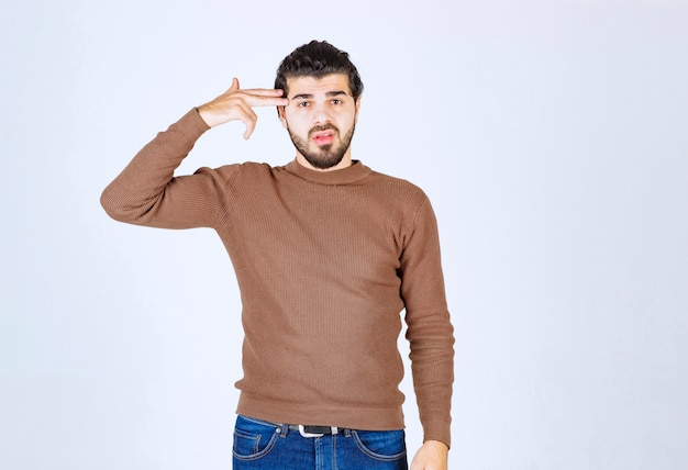 Young handsome man model keeping two fingers near head.