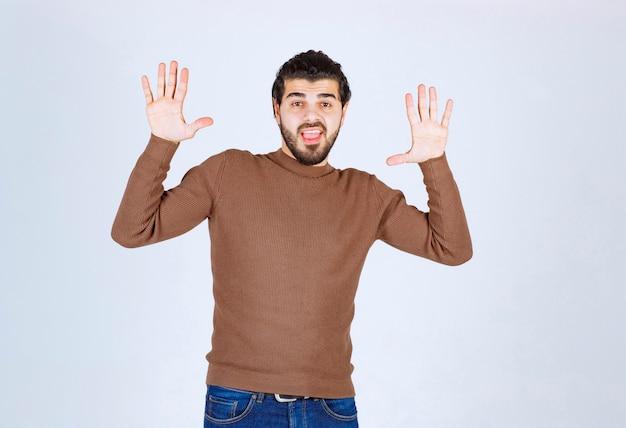 Un modello di giovane uomo bello che guarda e alza le mani.