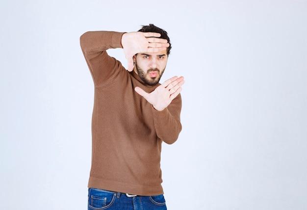 Молодой красавец модель, глядя через рамку, сформированную его руками.