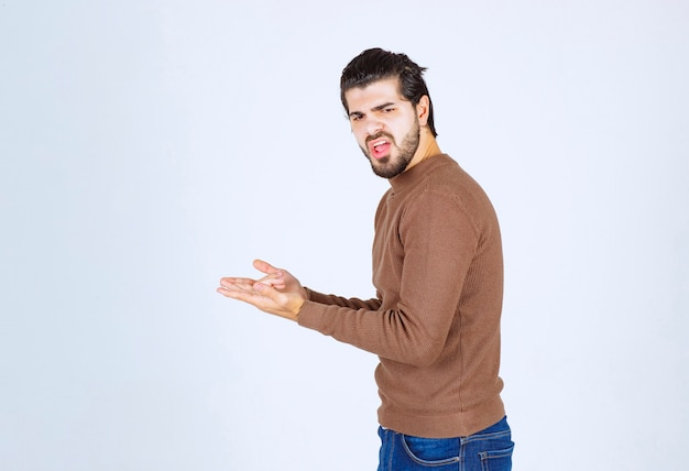 Young handsome man model standing in brown sweater and posing over white wall.