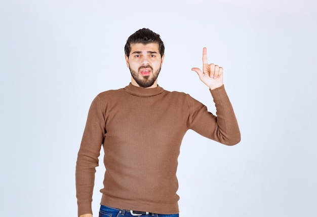 Young handsome man model standing and pointing up .