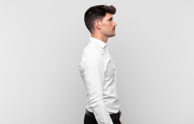 前方のスペースをコピーしようとしている、考えている、想像している、または空想にふける縦断ビューの若いハンサムな男
