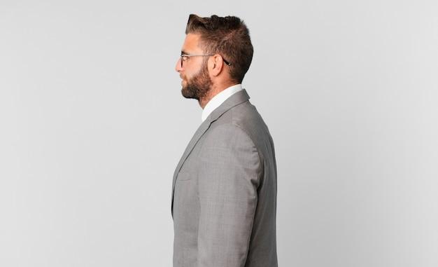 Молодой красивый мужчина на взгляде профиля мышления, воображения или мечтания. бизнес-концепция