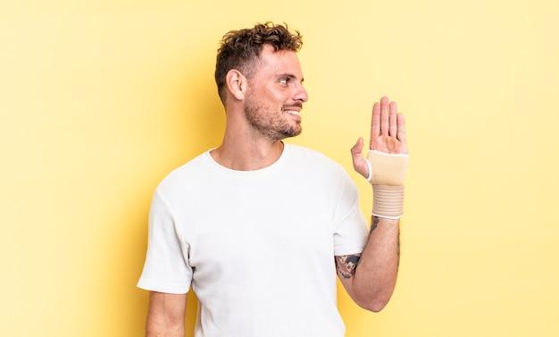 プロフィールビュー思考、想像、または空想の若いハンサムな男。手の包帯の概念
