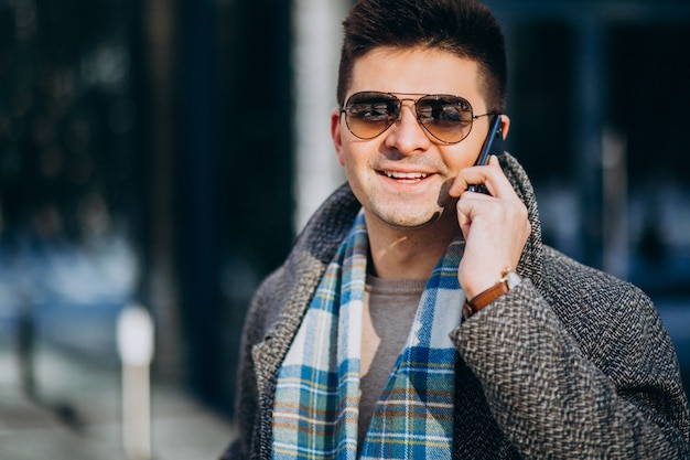 Young handsome man outside using phone