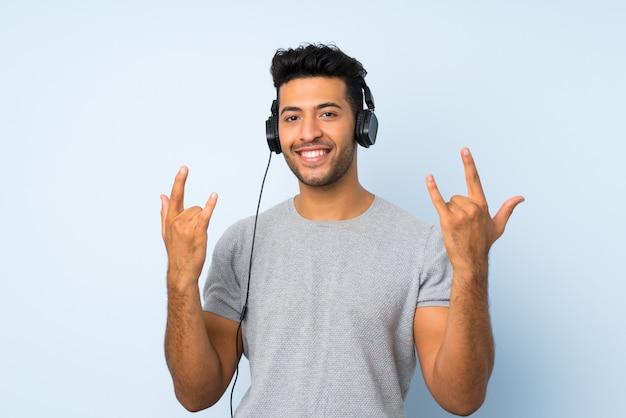 孤立した背景にヘッドフォンで携帯電話を使用して踊る若いハンサムな男