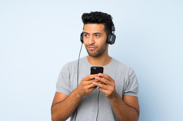 ヘッドフォンと思考と携帯電話を使用して孤立した背景の上の若いハンサムな男