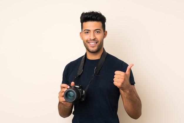 プロのカメラと親指のアップで孤立した背景の上の若いハンサムな男