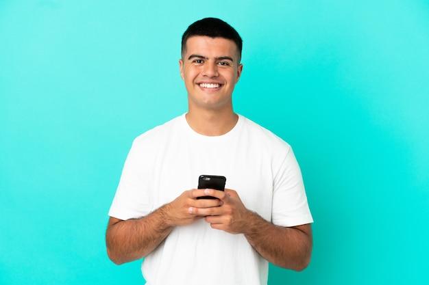 Молодой красавец на изолированном синем фоне смотрит в камеру и улыбается во время использования мобильного телефона