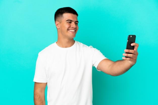 Молодой красавец на изолированном синем фоне, делая селфи с мобильным телефоном