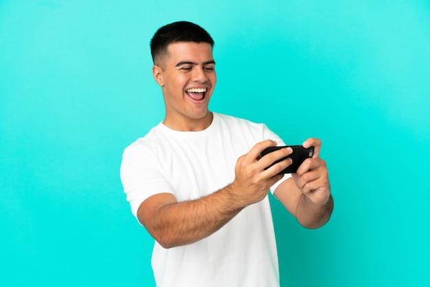 Молодой красавец на изолированном синем фоне играет с мобильным телефоном