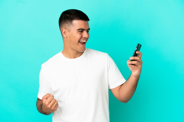 Молодой красавец на изолированном синем фоне, используя мобильный телефон и делая жест победы