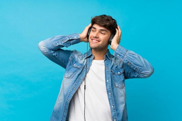 Молодой красивый мужчина на синем фоне с помощью мобильного телефона с наушниками