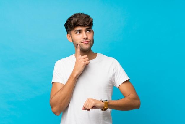 腕時計とアイデアを考えて分離の青い壁の上の若いハンサムな男