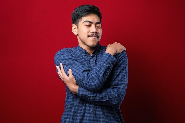 고립된 빨간색 배경 위에 젊고 잘생긴 남자가 행복하고 긍정적으로 자신을 껴안고 자신감 있게 웃고 있습니다. 자기애와 자기관리