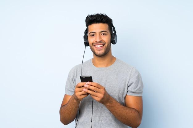 ヘッドフォンで携帯電話を使用して孤立した壁を越えて若いハンサムな男
