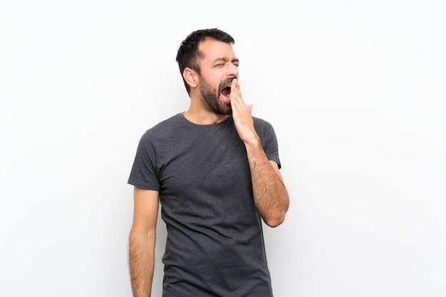 Молодой красавец над белой стене зевая и прикрывая широко открытый рот рукой