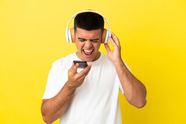 Молодой красавец на изолированном желтом фоне, слушает музыку с помощью мобильного телефона и поет