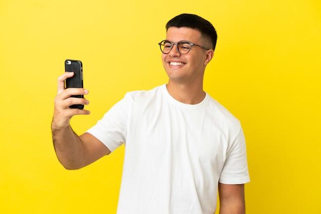 Молодой красавец на изолированном желтом фоне, делая селфи