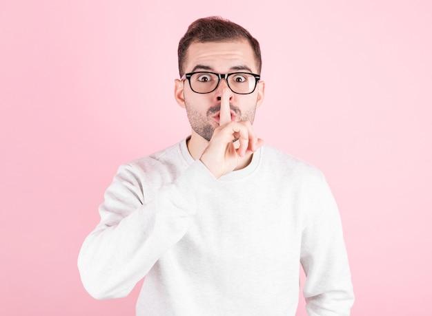 ピンクの背景の上の若いハンサムな男は、唇に指で静かにするように求めています。沈黙と秘密の概念。