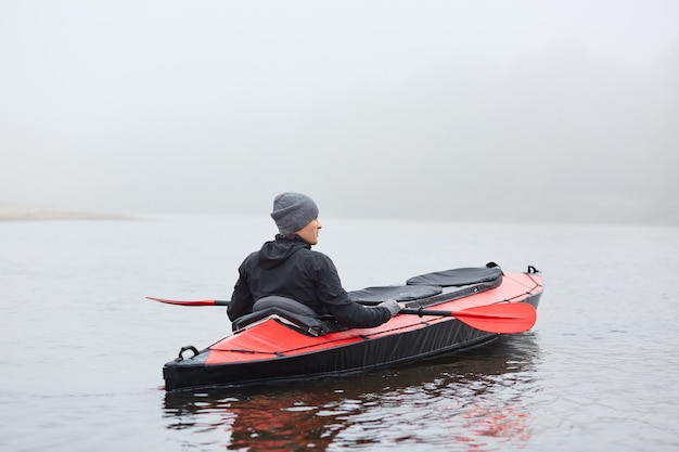 Young handsome man paddling canoe on cloudy day, canoeing on foggy day