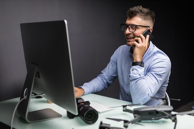 Молодой красивый мужчина-фотограф получает уведомление о доходах, сидя на своем рабочем месте в офисе