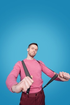 Young handsome man in pink casual pullover and pants stretching suspenders while standing