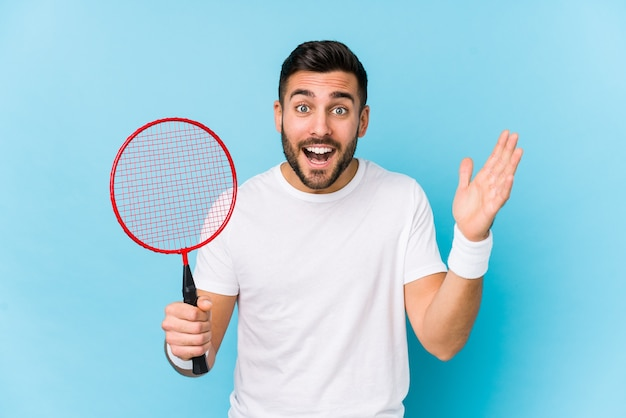 Young handsome man playing badminton isolated receiving a pleasant surprise, excited and raising hands.