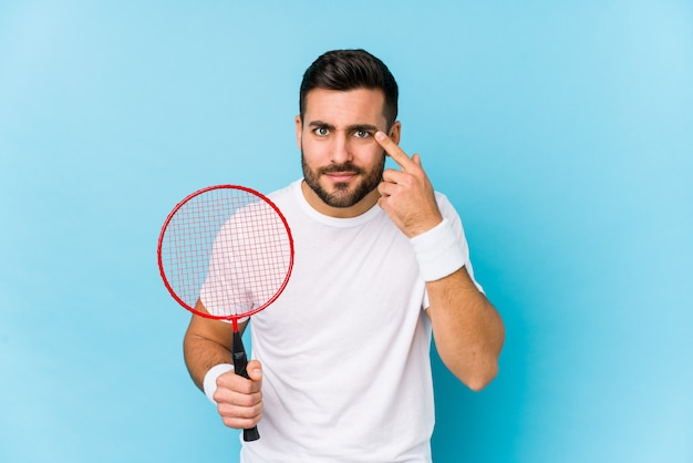 Young handsome man playing badminton showing a disappointment gesture with forefinger.