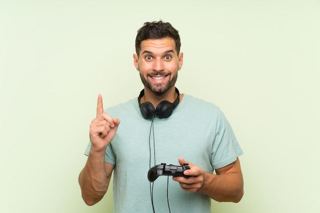 素晴らしいアイデアを指している孤立した緑の壁の上のビデオゲームコントローラーで遊ぶ若いハンサムな男