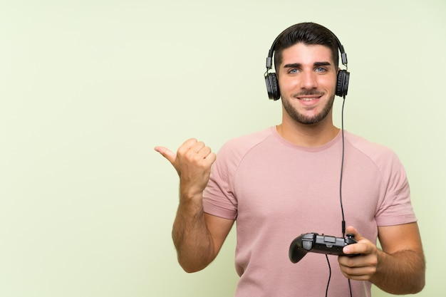 Young handsome man playing with a video game controller over isolated green wall