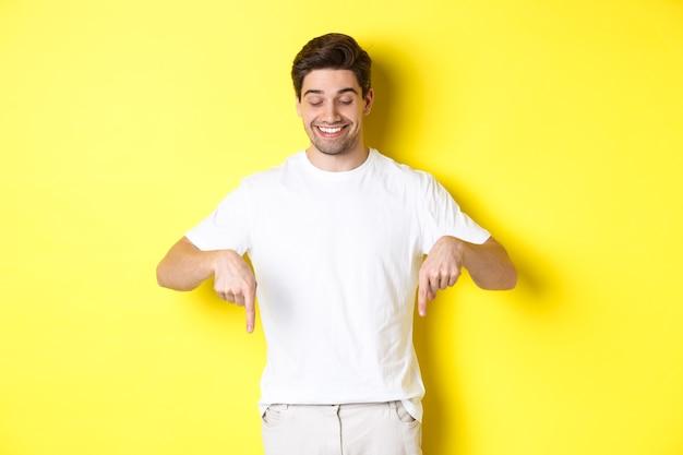 젊은 잘 생긴 남자를 가리키고 아래를 내려다 보면서, 프로 모션 제안을 확인, 노란색 배경 위에 서.