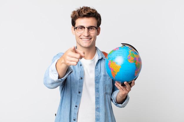 당신을 선택하는 카메라를 가리키는 젊은 잘생긴 남자. 세계 지도를 들고 있는 학생