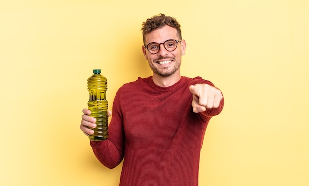 Young handsome man pointing at camera choosing you. olive oil concept