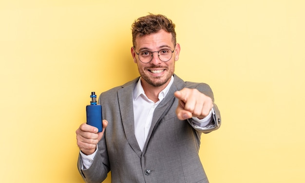 Young handsome man pointing at camera choosing you. vaporizer concept
