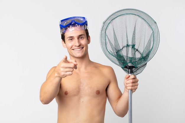 Young handsome man pointing at camera choosing you with goggles and a fishing net