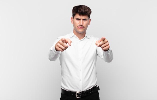 두 손가락과 화난 표정으로 앞으로 가리키는 젊은 잘 생긴 남자, 당신에게 의무를 다하라고 말합니다.