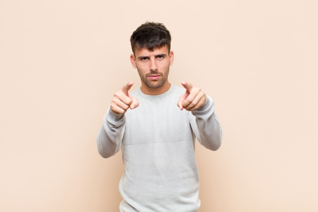 Young handsome man pointing forward with both fingers and angry expression, telling you to do your duty against warm wall