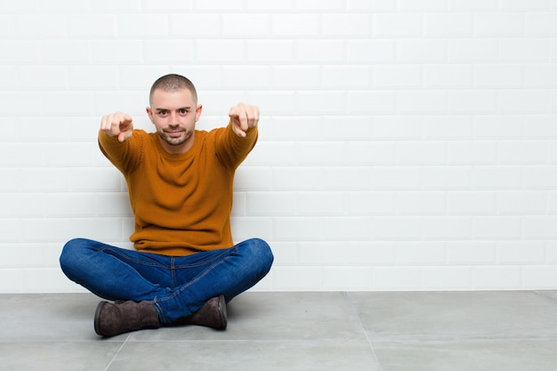 Young handsome man pointing forward with both fingers and angry expression, telling you to do your duty sitting on the floor