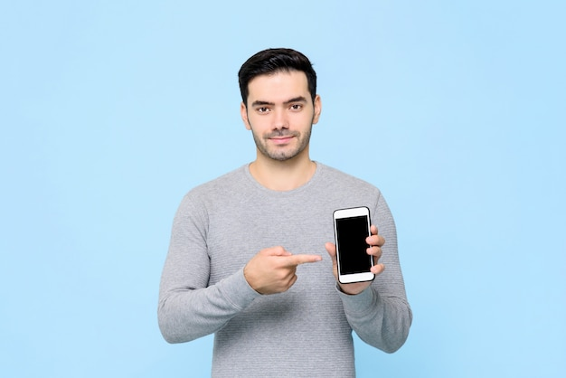 Young handsome man pointing to his mobile phone in hand isolated