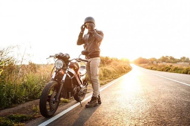 Молодой красавец позирует возле своего мотоцикла на сельской дороге.