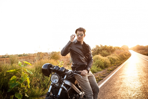Young handsome man posing near his motorbike at countryside road.
