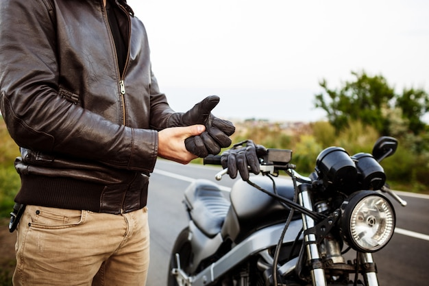 Young handsome man posing near his motorbike, wearing gloves.