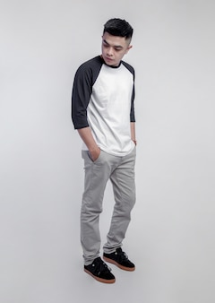 Young handsome man posing wearing raglan t-shirt  isolated on background