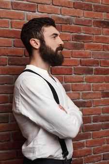 Young handsome man posing with crossed arms on brick wall.